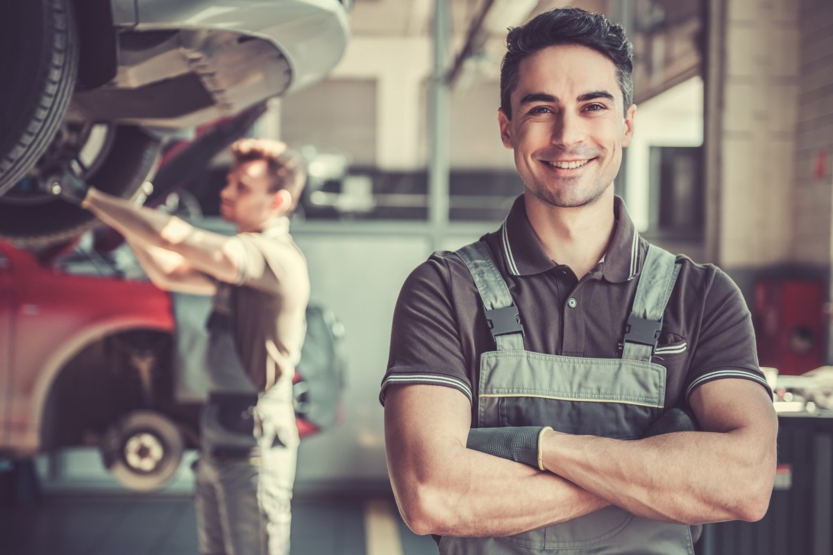 mechanic smiling in front of car on lift and another mechanic working on it